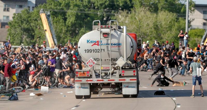 一輛油罐車竟筆直衝入在橋上的抗爭人群,民眾紛紛閃避。(路透)