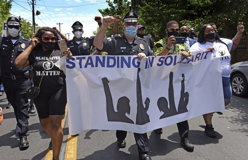 紐澤西州康敦縣警察局長懷索克與示威者一同拉起標語。(美聯社)