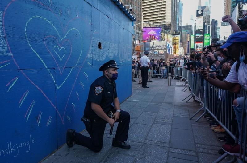 1名警察於紐約時代廣場屈膝跪地。(法新社)