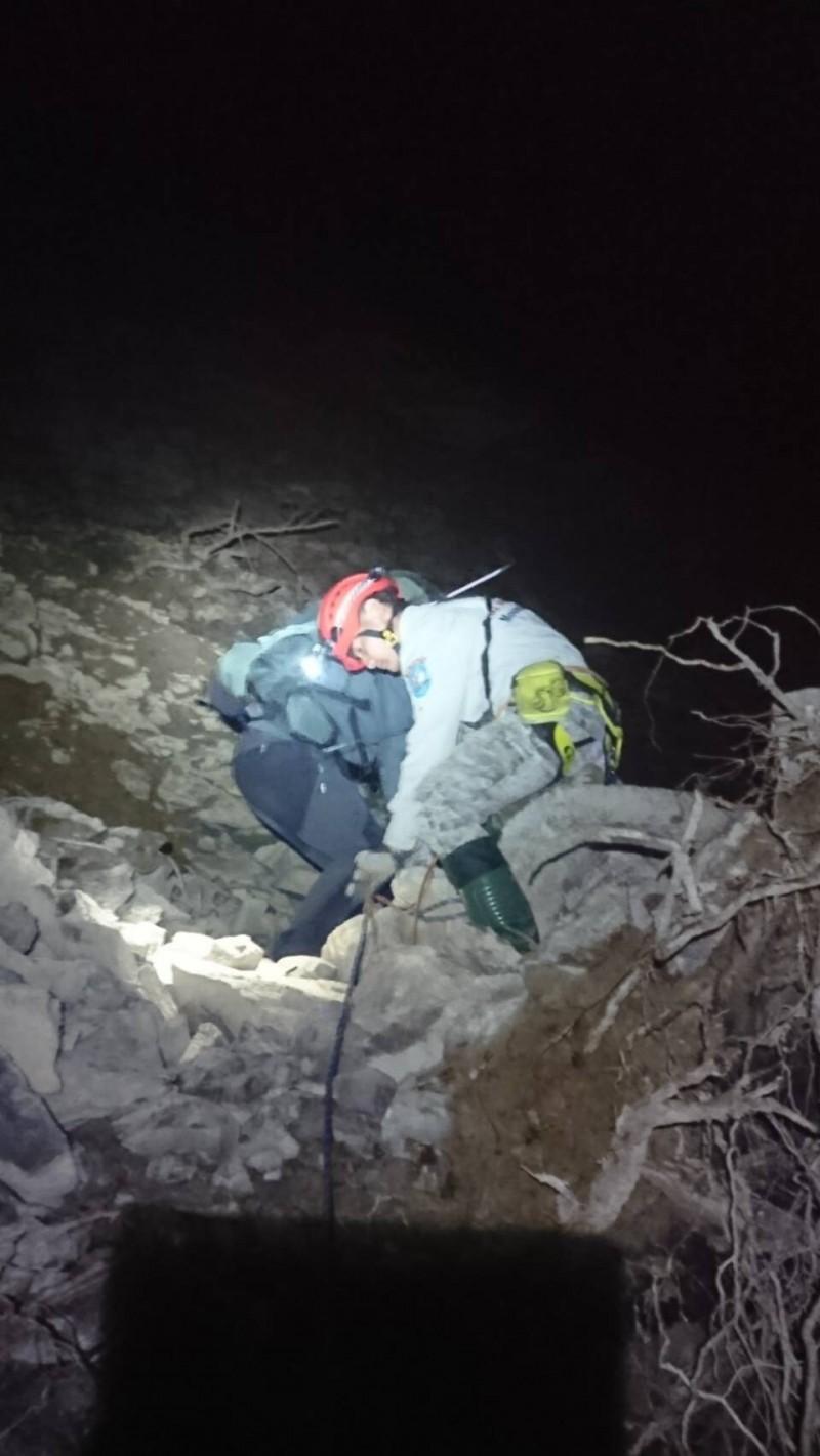 由於合歡溪步道山壁因連日降雨發生崩塌,救難人員架設繩索攀越崩塌處與登山隊會合,並協助脫困。(南投縣神鷹山區搜救隊提供)