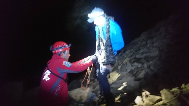 救難人員協助登山客繫妥繩索,協助攀越危險崩塌地點。(南投縣神鷹山區搜救隊提供)
