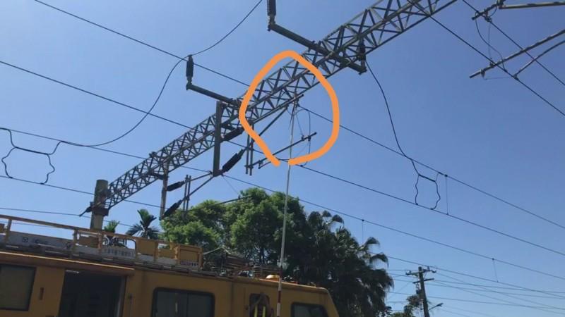 保育類黑眉錦蛇爬上電車線上桁架觸電死亡,電務段人員試圖將蛇勾下來。(台鐵提供)