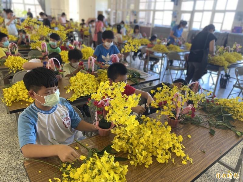 台中市花卉外銷受阻,市府舉辦校園花藝課程,外埔國小學童學習插花,直呼新鮮有趣。(記者張軒哲攝)