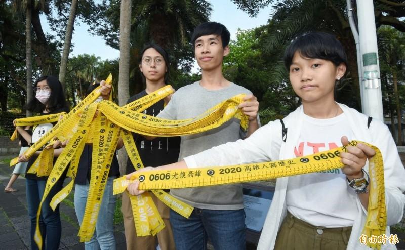台大、師大學生會會長3日傍晚在台灣大學大門口,發送民主黃絲帶,強調高雄是我們的故鄉、認同的所在,呼籲在台北的同學,一起站出來返鄉投票。 (記者劉信德攝)