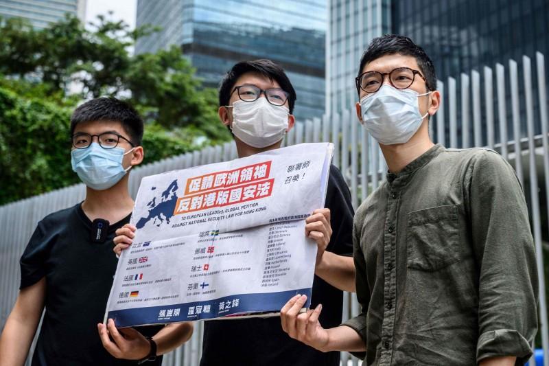 香港眾志的黃之鋒(圖左)、羅冠聰(圖右),以及民間外交網絡發言人張崑陽(圖中)發起聯署,呼籲歐洲各國領袖表態反對「港版國安法」,目標是10萬人聯署。(法新社)