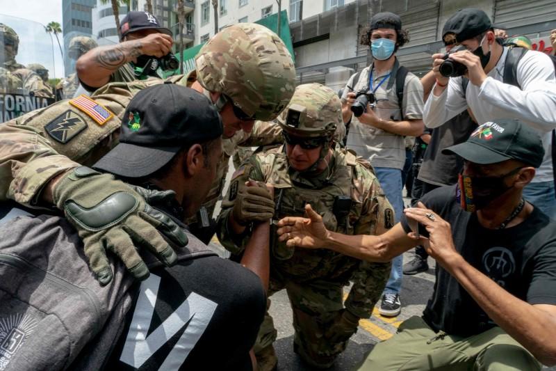 國民兵單膝跪地致意,展現與民同在氛圍。(法新社)