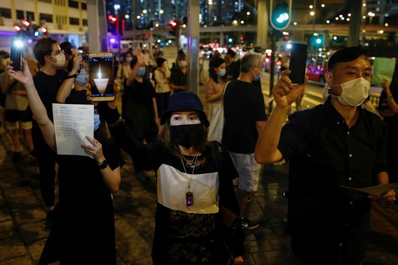明天是六四天安門事件31週年,今年港澳紀念活動遭禁,3日晚上港人上街舉辦參加相關活動,手機顯示燭光悼念六四死難者。(路透)
