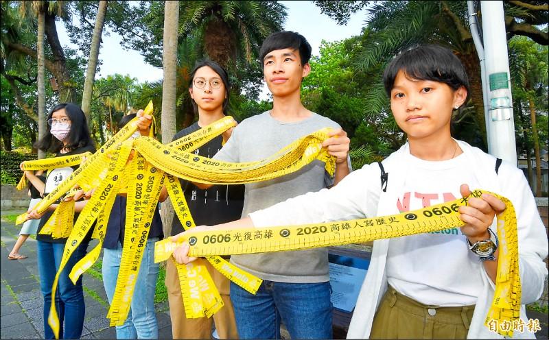 台大、師大學生會會長昨傍晚在台大門口,發送民主黃絲帶,呼籲在台北的同學,一起返鄉投票。(記者劉信德攝)