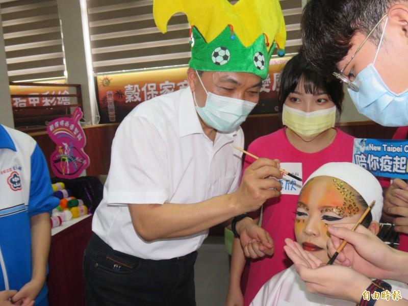 新北市長侯友宜在穀保家商時尚科學生協助下體驗人體彩繪。(記者陳心瑜攝)