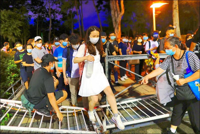 香港民眾昨踏過被拉倒在地的拒馬,進入維園參與六四悼念活動。(歐新社)
