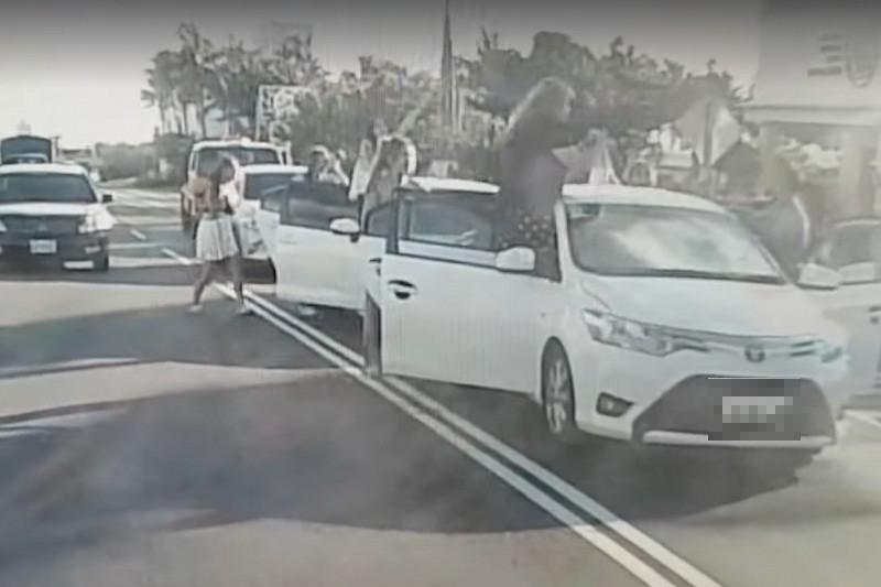 墾丁車道上車輛突開門,乘客下車嬉鬧,嚇壞路過駕駛人將挨罰。(記者蔡宗憲翻攝)