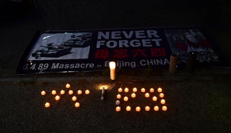 美國洛杉磯4日在中國領事館外舉行的「六四天安門事件」31週年紀念活動,以燭光排出「六四」,海報上寫著「永不遺忘」。(法新社)