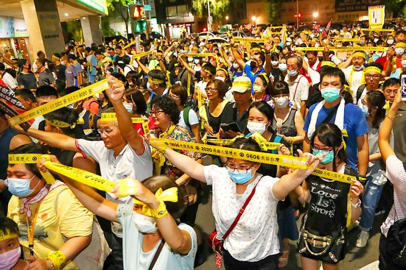 People hold up yellow ribbons of a campaign to recall Kaohsiung Mayor Han Kuo-yu at the Kaohsiung MRT metropolitan railway system's Formosa Boulevard Station last night at a final rally before the recall election today. Photo: CNA