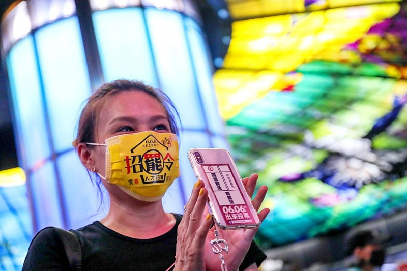 A woman shows her self-made sticker and mask to campaign for recalling Kaohsiung Mayor Han Kuo-yu yesterday at Kaohsiung Mass Rapid Transit's Formosa Boulevard Station during the final rally before the recall vote. Photo: CNA