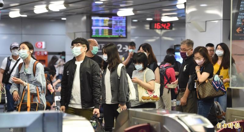 高雄市長韓國瑜罷免案本週六投票,許多民眾都打算返鄉投票,台北車站高鐵閘門口,在五日傍晚湧現人潮,戴著口罩排隊通過體溫篩檢站,準備搭乘高鐵列車。 (記者劉信德攝)
