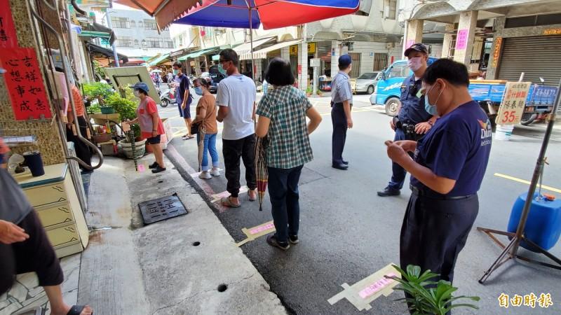 選務人員在投票所外不時提醒民眾要戴好口罩,保持一公尺的社交距離。(記者張忠義攝)