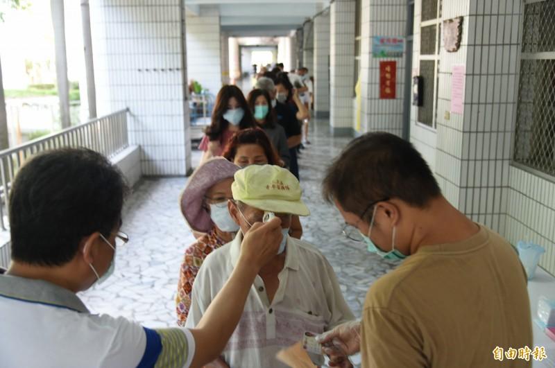工作人員對進入投票民眾都要量額溫,並仔細核對證件。(記者張忠義攝)