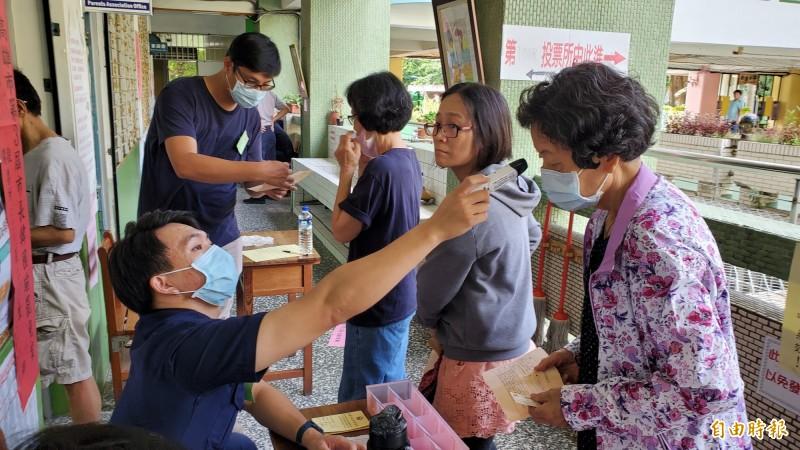 工作人員貼心提醒民眾要戴好口罩,並配合量測體溫才能順利進入投票所投票。(記者張忠義攝)