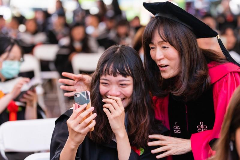 成大校長蘇慧貞與畢業生一起玩手機自拍合影留念。(成功大學提供)