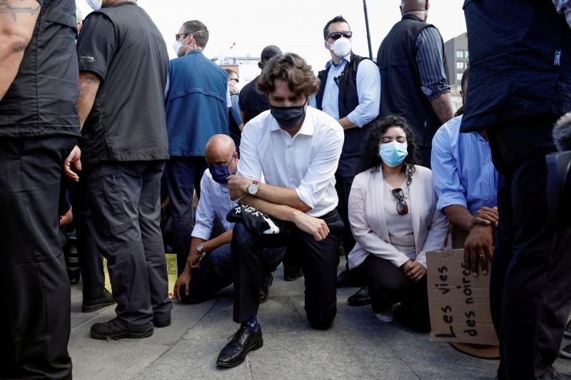 加拿大總理杜魯道在反種族主義集會現場,與示威者一同單膝下跪。(路透)