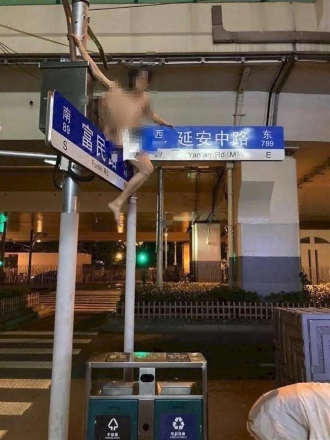 中國上海25歲徐姓男子酒後脫序,裸身爬上路牌跨坐任人拍攝。(圖翻攝自微信)