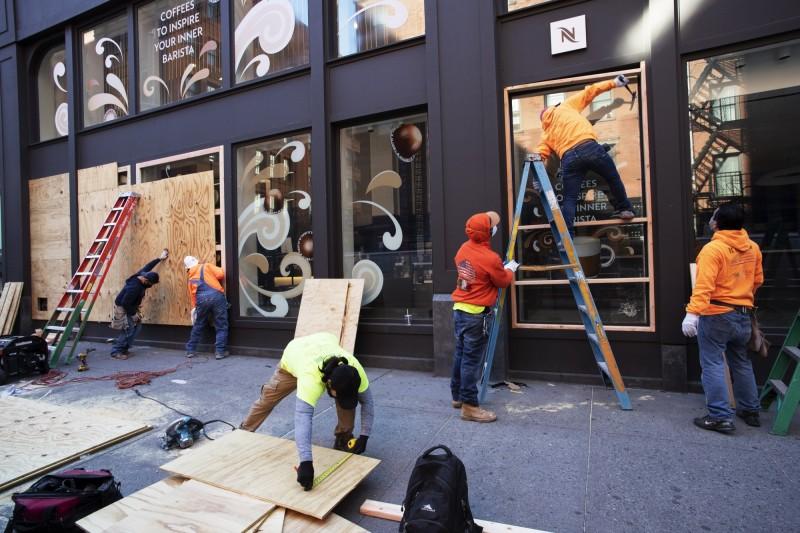 店家在櫥窗外釘上木板。(美聯社)