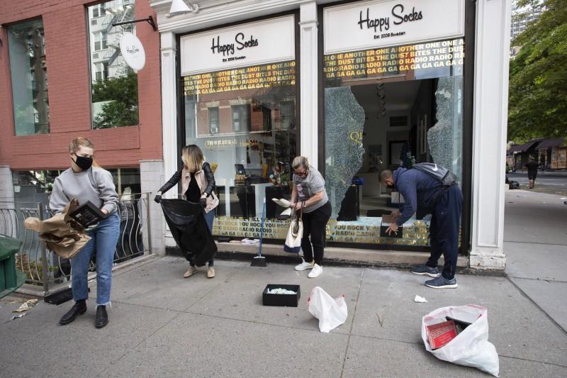 志工協助清理櫥窗被打破後的碎玻璃。(美聯社)