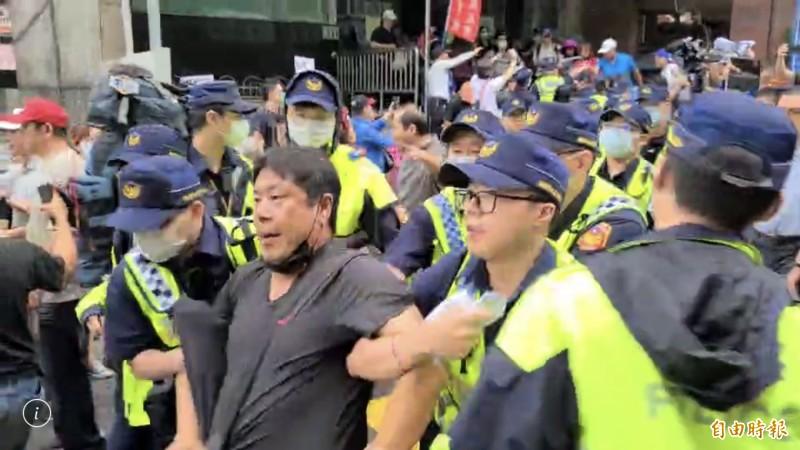韓粉集結王浩宇服務處丟雞蛋、砸水球,「杏仁哥」涉嫌丟雞蛋被警察帶走。(記者李容萍攝)