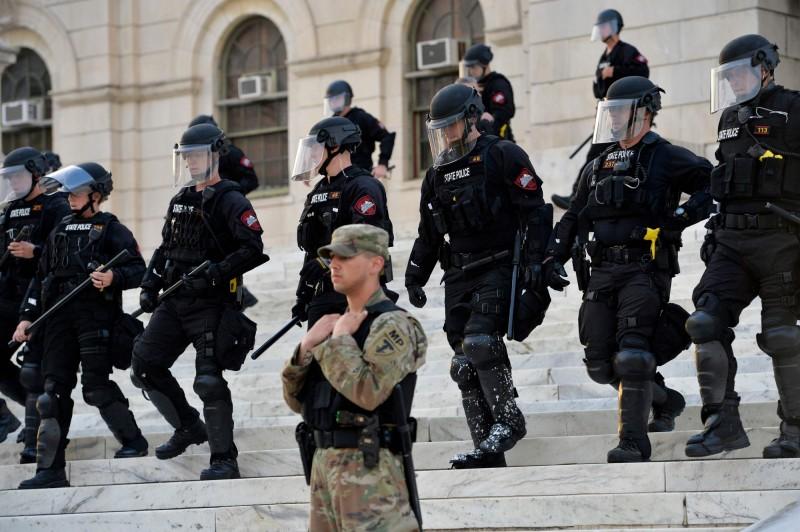 美國羅德島州1名非裔消防員,近日值班時穿著制服坐在消防局外的車輛內,卻有警察持槍不斷向他靠近,他見情況不妙立即大喊「我是自己人,不要開槍!」。羅德島鎮暴警察與國民警衛隊示意圖。(法新社)