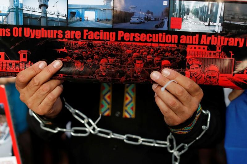有曾被關押在新疆「再教育營」的維吾爾人指控,中國官方將70多條「罪行」羅列為表格,強迫被押者承認,否則「將永遠待在營中」。圖為2019年新疆維吾爾人在日本大阪G20會場外抗議中國「再教育營」暴政。(路透資料照)