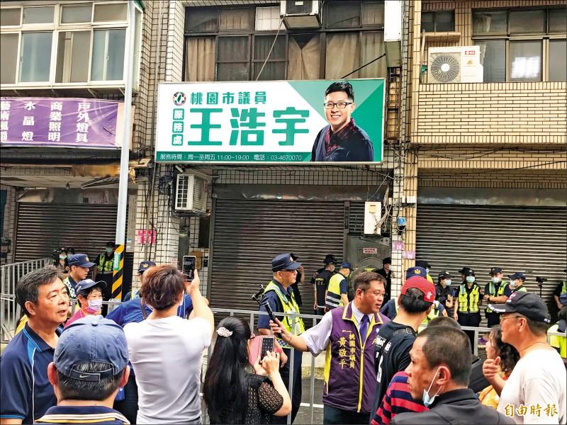 群眾昨在王浩宇服務處前丟雞蛋、撒冥紙抗議,警方拉起鐵柵欄等阻隔。(記者李容萍攝)