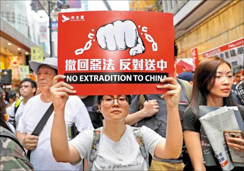 一名去年6月9日參與遊行的示威者舉起「撤回惡法、反對送中」標語。(美聯社檔案照)