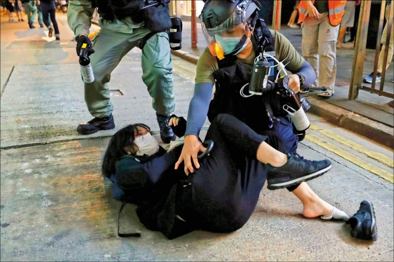 警方在多處封路、攔查參與遊行的民眾,在德輔道中發射胡椒球彈,一名示威者被壓制在地。(路透)