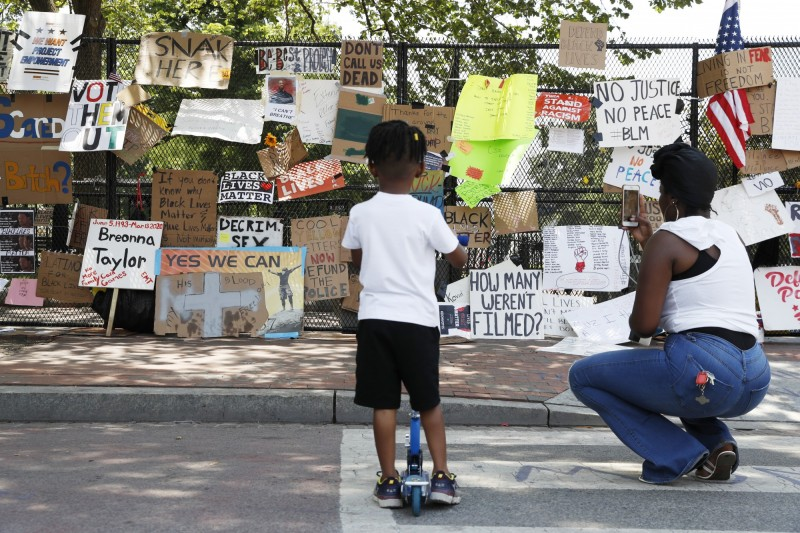 自從抗議民眾6月5日曾一度突破圍籬衝進白宮草皮,負責管理白宮的美國國家公園管理局與特勤局在白宮和前方的拉斐特公園外圍架起高達2.4公尺的黑色鐵柵欄,反而被民眾掛滿各種抗議標語。(美聯社)