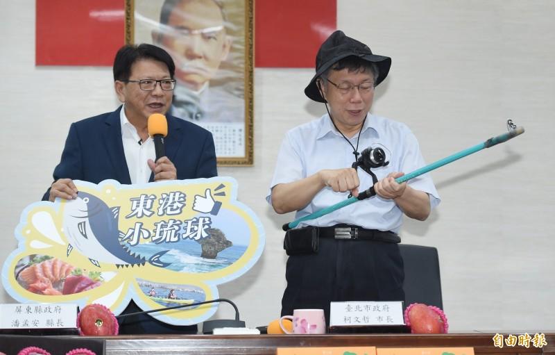 台北市長柯文哲(右)出席台北市與屏東縣交流活動,屏東縣長潘孟安(左)致贈柯釣魚竿、漁夫帽。(記者廖振輝攝)