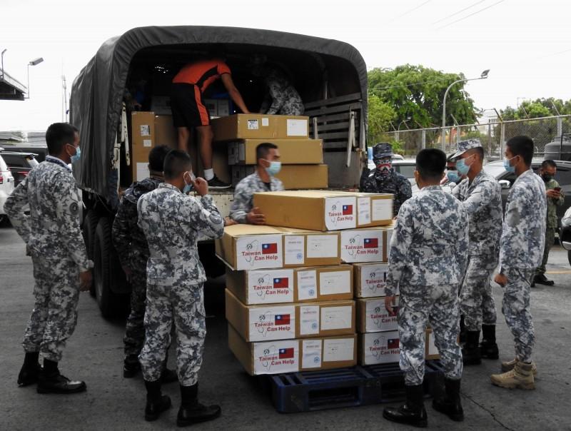 繼捐贈30萬片口罩後,台灣11日再捐出50萬片外科口罩、5萬片N95口罩、2萬件隔離衣和5000件防護衣等抗疫物資給菲律賓。圖為菲律賓海巡署人員搬運捐贈物資。(中央社)