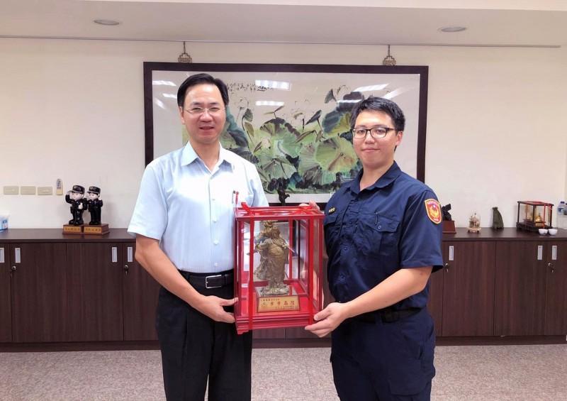 被同事稱為「哆啦A夢」的警員鐘柏榕(右),今天獲草屯警分局長贈送關公雕像,祝福他步步高陞。(草屯警分局提供)