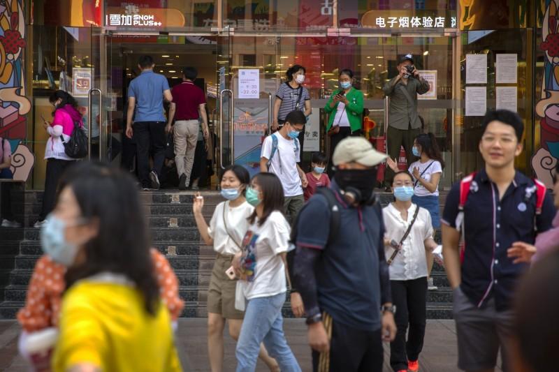 中國北京市時隔56天再現本土病例。圖為北京民眾戴口罩防疫。(美聯社)