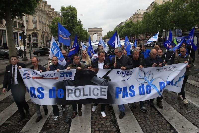 法國警察今(12日)在香榭大道遊行抗議,認為鎖喉的限制「太過了」,政府並未給予警方應有的支持。(美聯社)