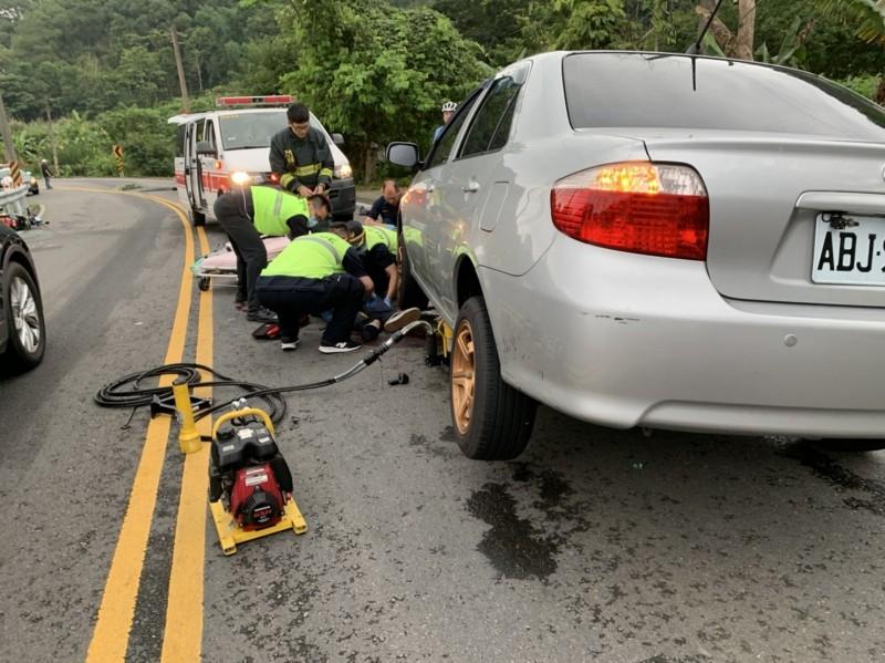 消防救護人員協助受困車底的機車騎士脫困,但患者被救出時已失去呼吸和心跳,送醫搶救中。(記者廖雪茹翻攝)
