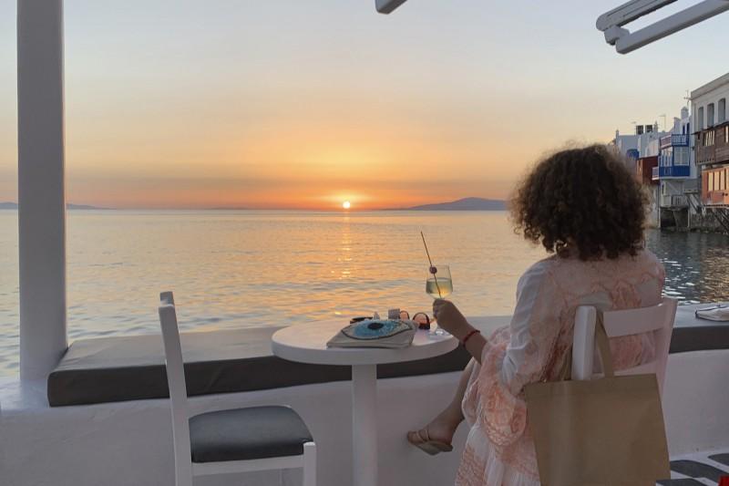 希臘政府宣布,從英國來的班機延後至6月30日以後才能入境停靠。圖為1名旅客在有「小威尼斯」之稱的米科諾斯島城鎮賞夕陽。(美聯社)