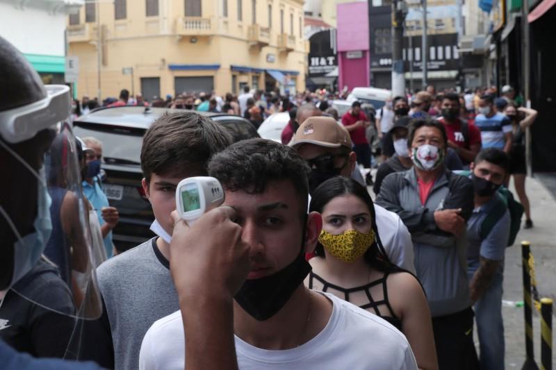 巴西染疫死亡人數超越英國,成為全球第二高。圖為巴西聖保羅民眾排隊等候進入購物中心。(路透)