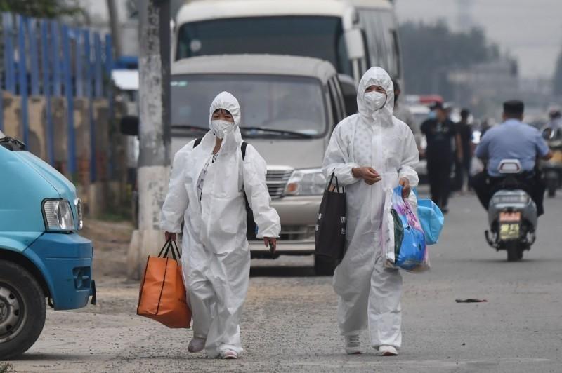 北京疾病預防控制中心副主任龐星火今召開第116場武漢肺炎疫情防控工作記者會,宣布北京市14日上午0時至7時,新增8名確診病例,且均與豐台區的新發地市場有關。圖為新發地市場爆發疫情後,有穿著全套防護衣的人員進駐市場。(法新社)