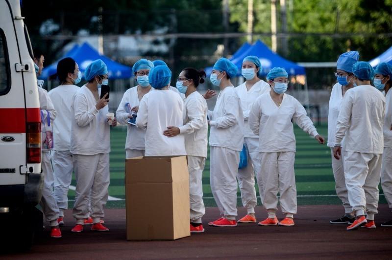 中國北京武漢肺炎(新型冠狀病毒病,COVID-19)疫情復燃,當地多個市場都爆發群聚感染。北京市官方今(15)日宣布,北京全市社區防控工作進入「戰時狀態」,並展開「敲門行動」大排查。圖為醫護人員準備對「新發地批發市場」附近的居民做病毒篩檢。(法新社)
