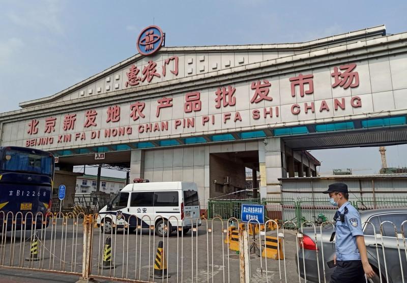 北京新發地農產品批發市場傳出武漢肺炎疫情,入口處大門深鎖還有警方站崗。(路透)
