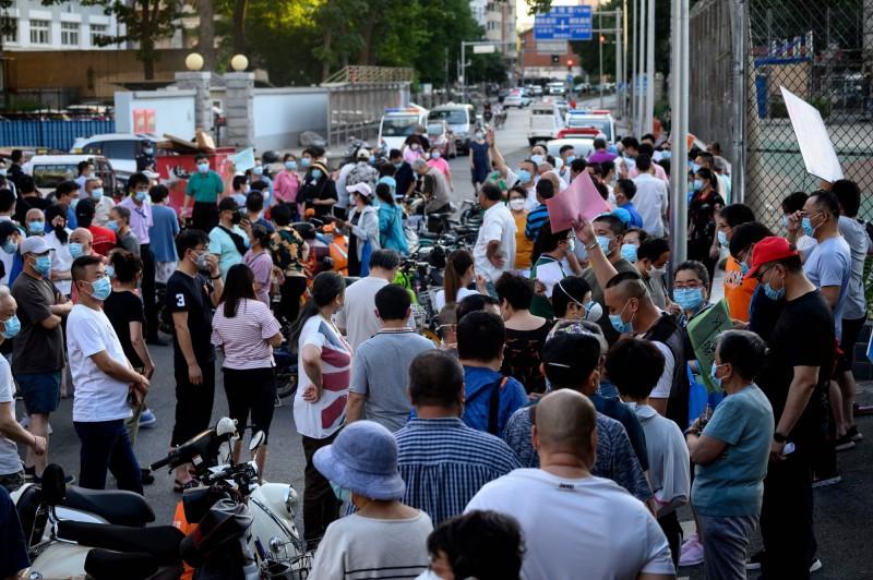 曾至「新發地批發市場」的北京市民排隊接受病毒篩檢。(法新社)