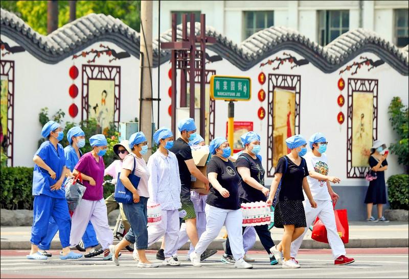 北京市一群戴著口罩的醫護人員正前往篩檢中心,準備為曾到新發地批發市場,或曾接觸高風險族群的民眾進行篩檢。(法新社)
