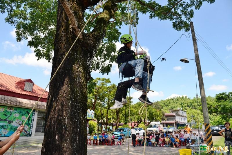 新威國小今年畢業生在全校的加油聲中,攀樹摘旗換畢業證書。(記者許麗娟攝)