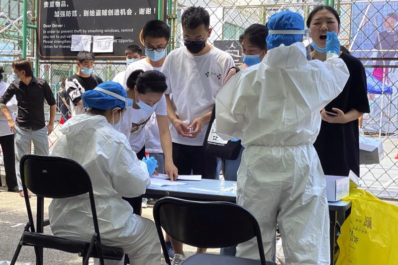北京疫情升溫,當地醫護人員採集「新發地批發市場」相關人員、附近居民的咽喉樣本。(美聯社)