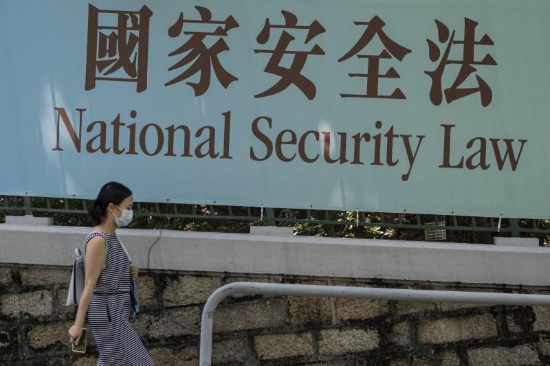 香港國安法壓境。19日一名港人走過街頭宣傳國安法的看板。(彭博)